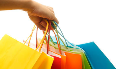 A woman hand carrying a bunch of colorful shopping bags