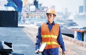 Man walking on shipyard with notes