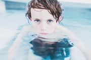 Bilde av gutt i basseng med alvorlig blikk