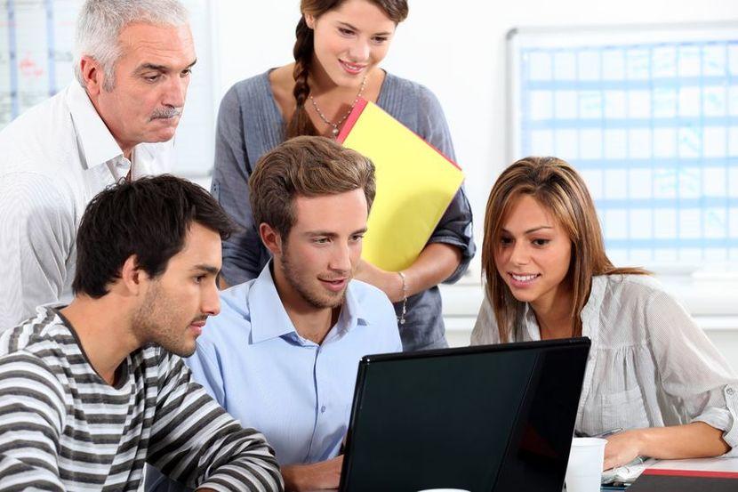 13839804 - informal team of people sitting round a laptop computer