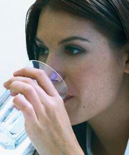 Dame drikker vann fra glass