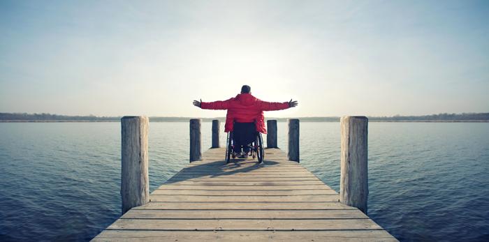 Bilde av mann i rullestol med åpne armer som ser utover horisonten.