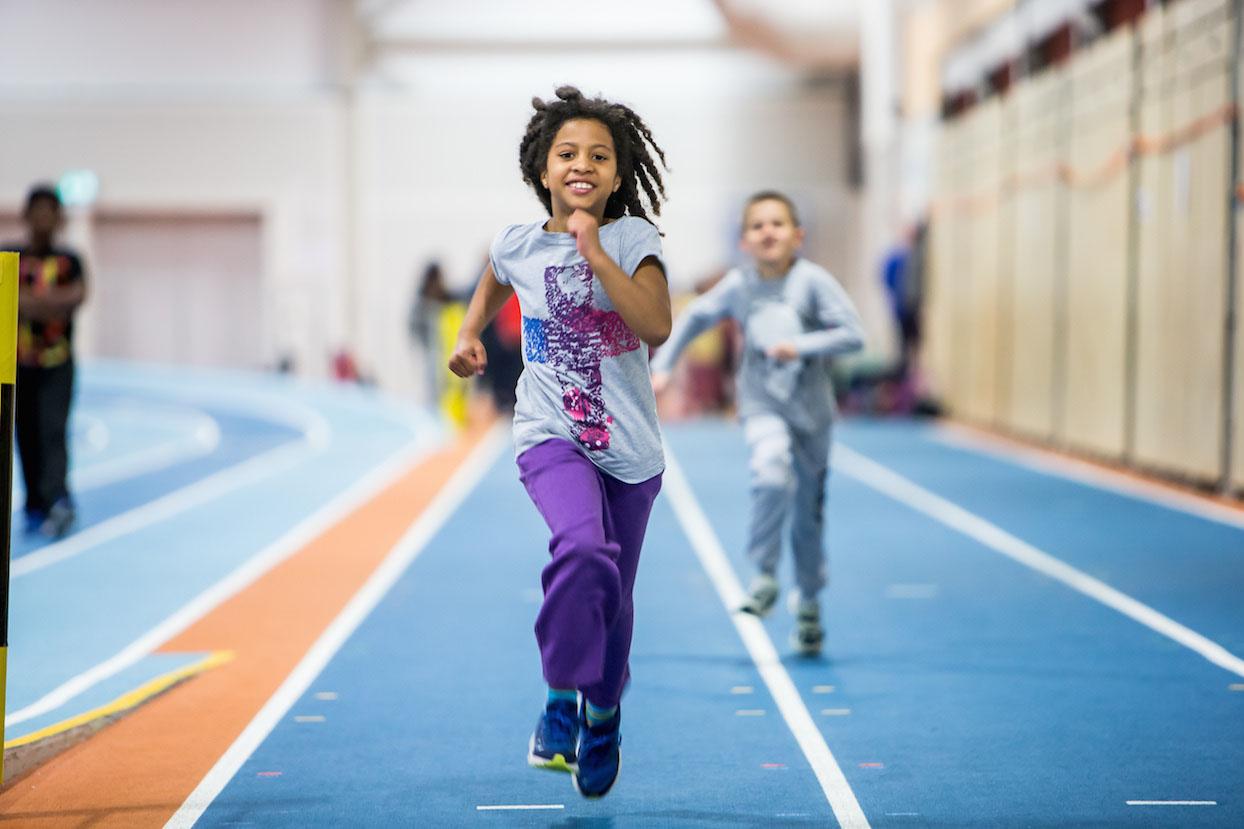 Bilde av ung jente som løper mot fotografen