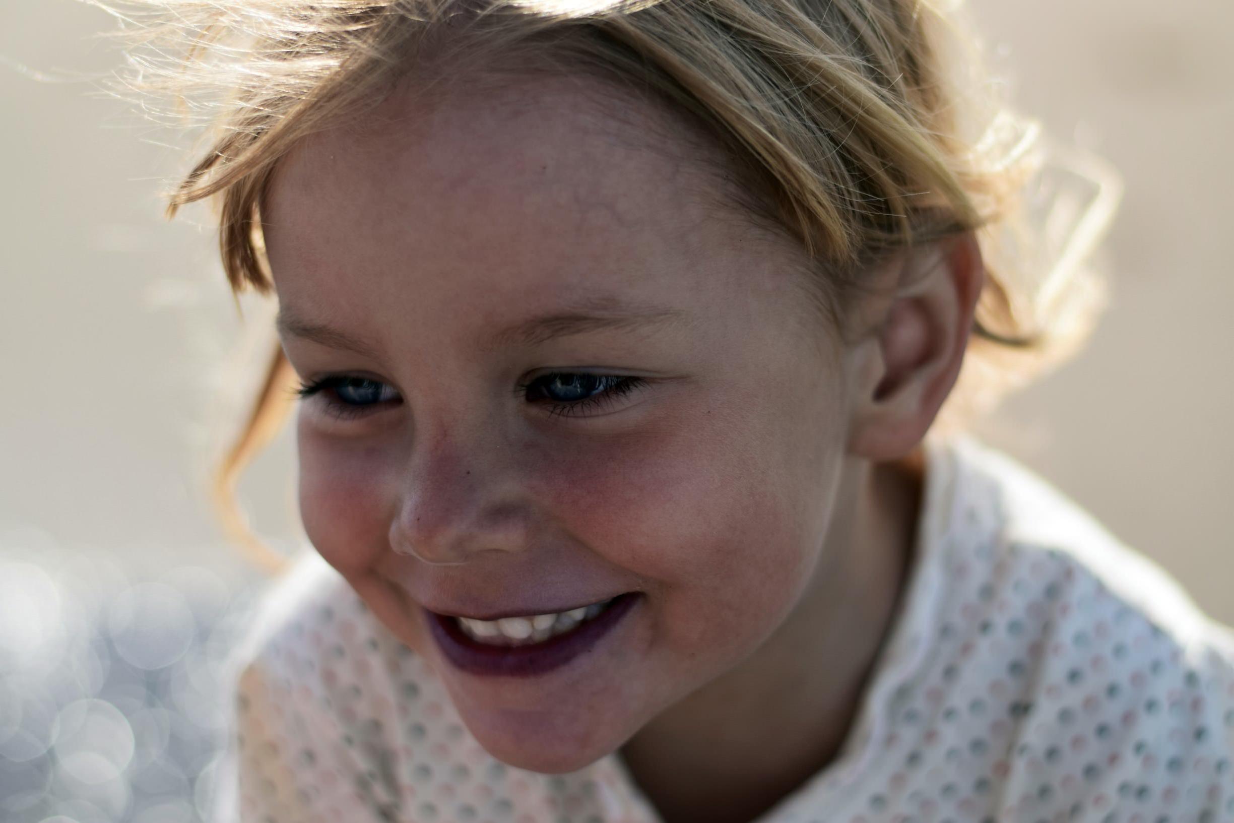 Nærbilde av ansiktet til en glad jente på rundt fire år