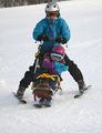 Bilde av en jente på sitski med en voksen som styrer, bak