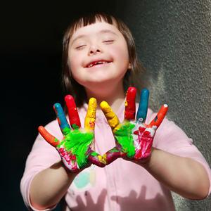 Bilde av glad jente med fargerik maling på fingrene