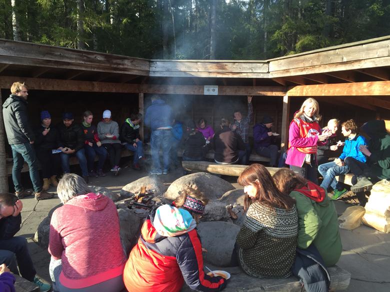 Bilde av mennesker som sitter ved en gapahuk og brenner bål