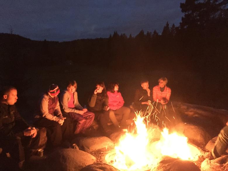 Kveldsbilde av mennesker rundt et flammende bål