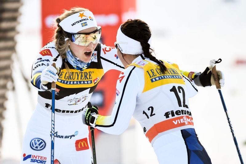 Stina Nilsson och Charlotte Kalla jublar efter målgång på masstarten i Val di Fiemme. FOTO: Carl Sandin/Bildbyrån.