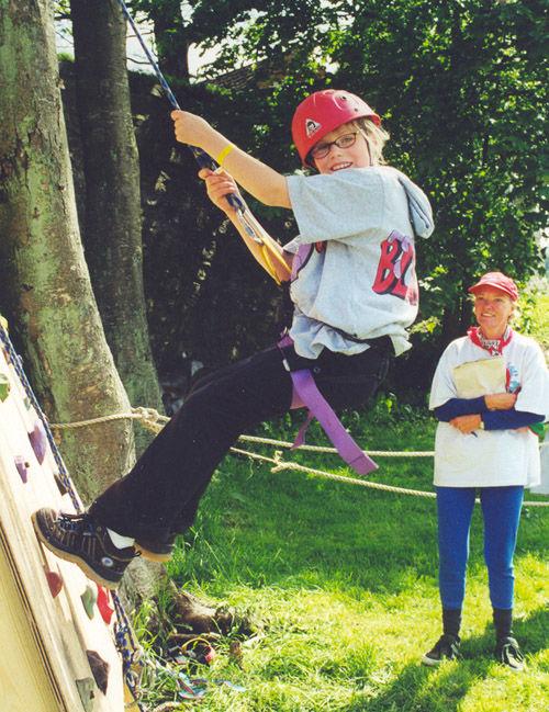 Bilde av ung jente som klatrer med klatreutstyr og tau