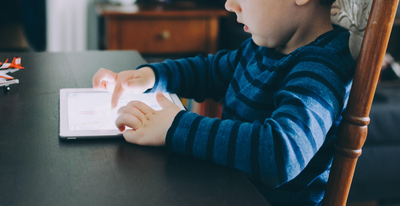 En liten gutt med nettbrett foran seg på et bord