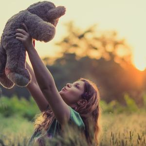 Ung jente som holder en bamse opp i lufta