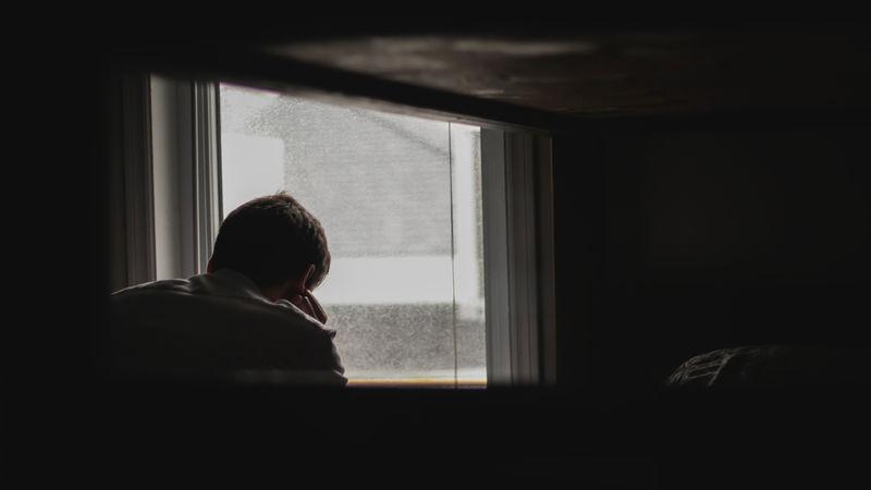 Mann som sitter i et mørkt rom foran et vindu