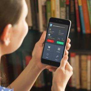 Bilde av en kvinne som holder en smarttelefon med appen Tjenesteshop
