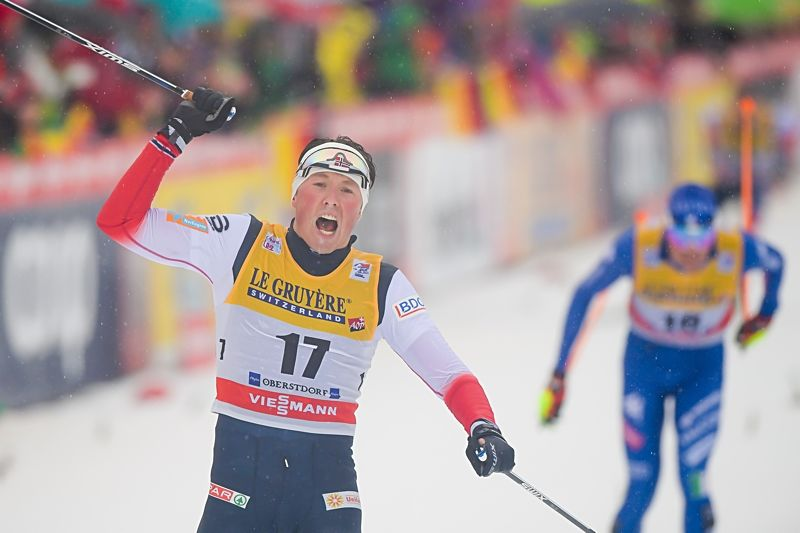 Emil Iversen jublar efter att ha spurtat hem segern på masstarten i Oberstdorf. I bakgrunden trean, italienaren Francesco de Fabiani. FOTO: Jon Olav Nesvold/Bildbyrån.