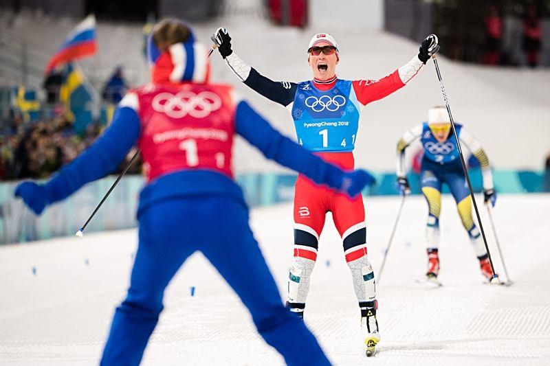 Marit Björgen jublar över guld och där bakom kommer Stina Nilsson i silverposition. FOTO: Joel Marklund/Bildbyrån.