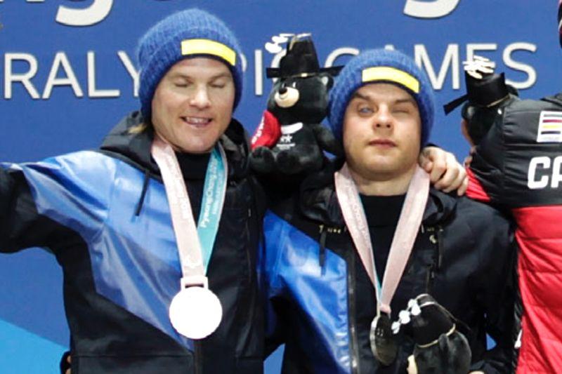 Zebastian Modin tillsammans med Robin Bryntesson på prispallen vid Paralympics i Sydkorea. Nu söker Zebastian nya guider till sitt team i sin fortsatta satsning.