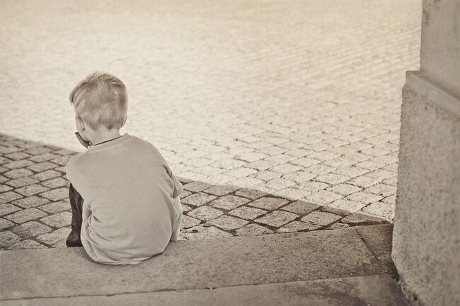 Gutt sitter alene på trapp