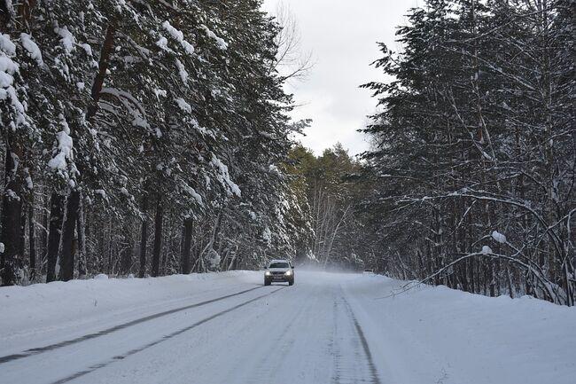 Bil kjører på vinterveg