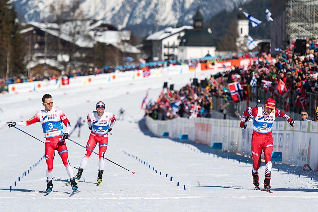 Sjur Röthe korsar mållinjen som världsmästare precis före Alexander Bolshunov och med Martin Johnsrud Sundby strax bakom. FOTO: Joel Marklund/Bildbyrån.
