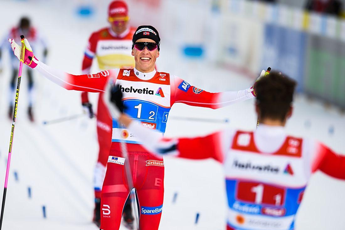 Johannes Hösflot Kläbo tas emot av Emil Iversen efter att ha spurtat hem guld till Norge i sprintstafetten. I bakgrunden syns Calle Halfvarsson på väg mot fjärde plats för Sverige. FOTO: Vegard Wivestad Grött/Bildbyrån.