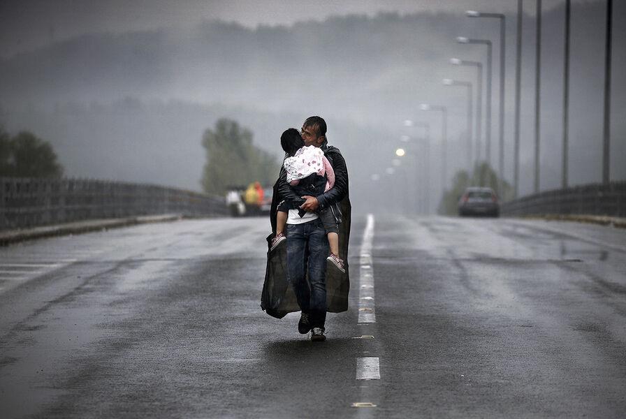 Idomeni, Greece 2015 © Yannis Behrakis / Reuters A Syrian refugee kisses his daughter as he walks through a rainstorm towards Greece's border with North Macedonia, near the Greek village of Idomeni, September 10, 2015.