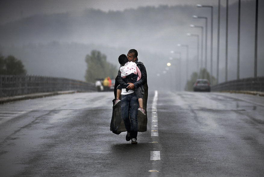 Idomeni, Greece 2015 © Yannis Behrakis / Reuters A Syrian refugee kisses his daughter as he walks through a rainstorm towards Greece's border with North Macedonia, near the Greek village of Idomeni, September 10, 2015.