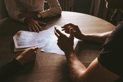 Bilde av tre stykker rundt et bord som har møte og diskuterer.