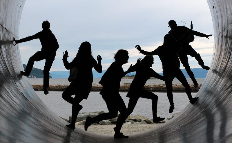 Silhuetter av seks ungdommer inni et stort rør