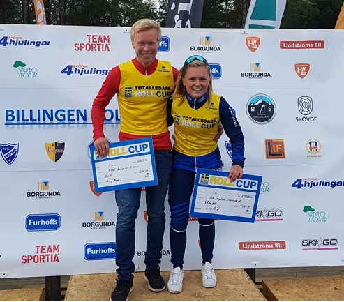 Alfred Buskqvist och Julia Angelsiöö, totalvinnare av STS Roll Cup 2019, med vinnarcheckar och vinnarvästar. FOTO: Svenska skidförbundet.