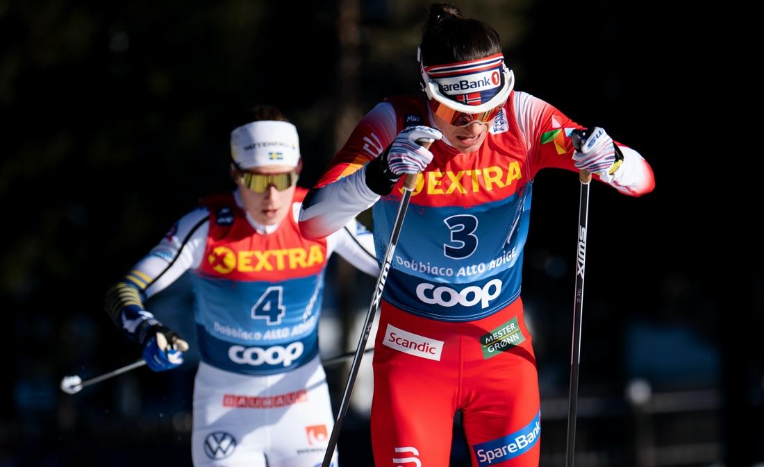 Ebba Andersson i rygg på Heidi Weng under jaktstartloppet i Toblach. FOTO: Bildbyrån/Daniel Bergeld.