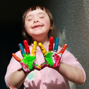 Bilde av en glad jente som holder sine åpne malte hender opp foran seg