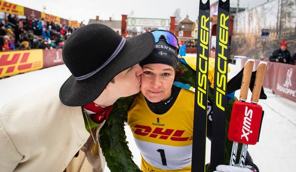Kransmasen Daniel Duhlbo ger Britta Johansson Norgren segerkyssen efter hennes fjärde seger i Tjevasan. FOTO: Vasaloppet.