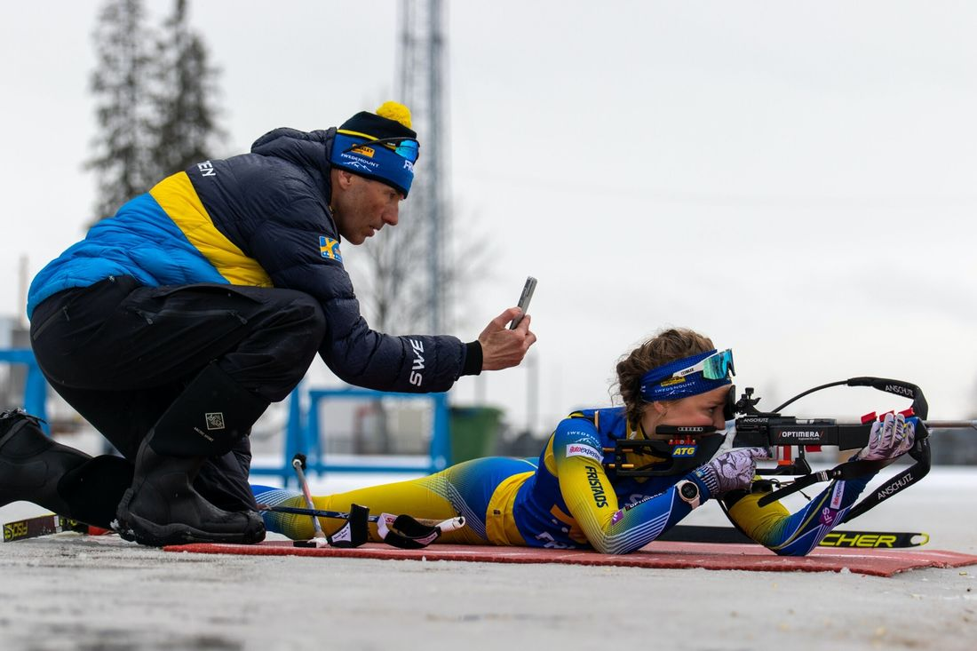 Stina Nilsson har valt Lima SKG som klubb i sin nya sport skidskytte men fortsätter som längdåkare i IFK Mora SK. Här är Stina på skjutvallen övervakad av skyttetränaren Jean-Marc Chabloz. FOTO: Håkan Blidberg/Svenska skidskytteförbundet.