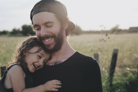 Bilde av en smilende mann som holder en leende jente på armen