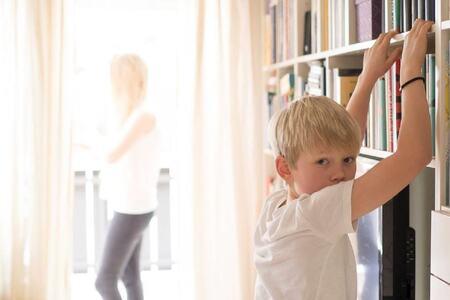 Bilde av gutt som lener seg mot en bokhylle mens han ser rett på fotografen