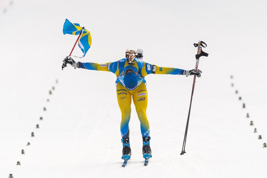 Sebastian Samuelsson med svensk flagga över mållinjen. FOTO: Joel Marklund/Bildbyrån.