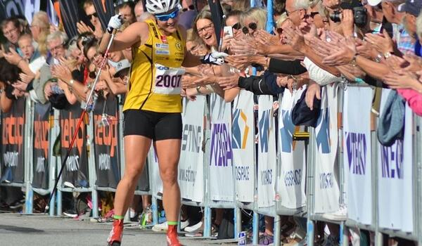 Hanna Falk tar emot folkets jubel på upploppet när hon tag andra raka segern i Alliansloppet 2016. Nu ser det ut att bli långlopp även vintertid för Falk. FOTO: Johan Trygg/Längd.se.