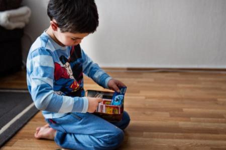 Bilde av en liten gutt i pysj som leker på gulvet
