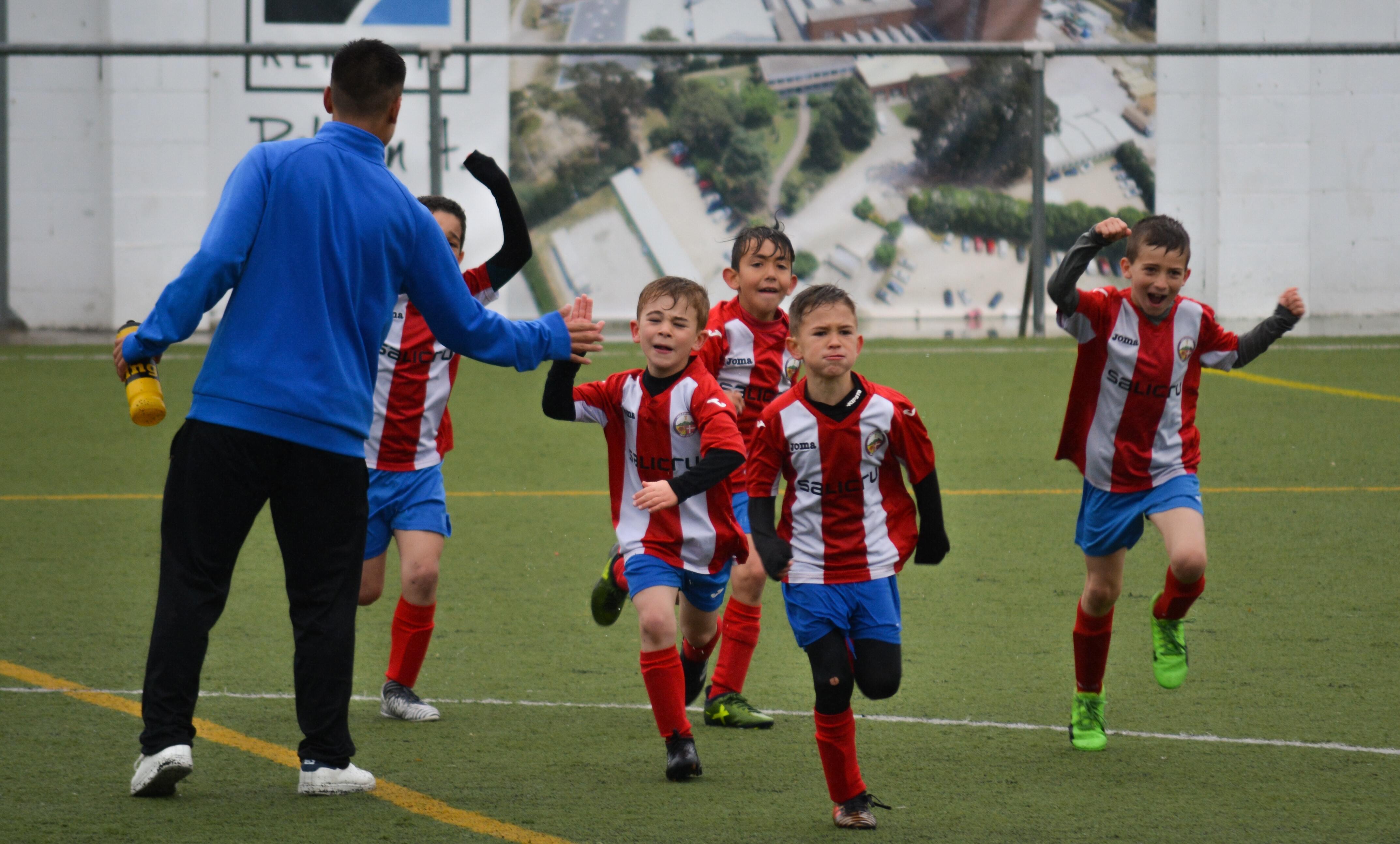 Glade gutter som spiller fotball